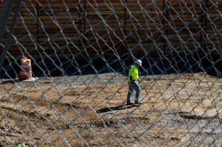 A worker walks through the South Crouse Avenue construction site. Photo taken Aug. 8, 2017